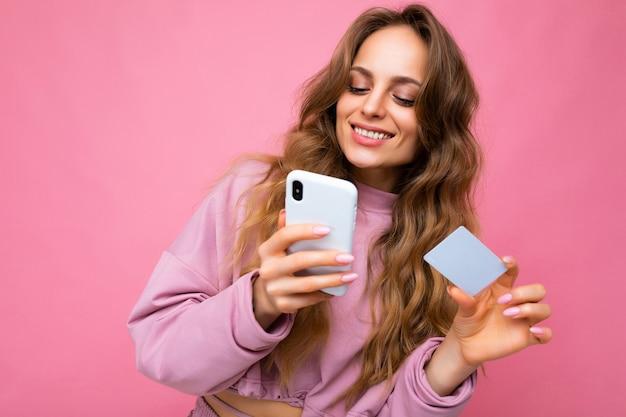 분홍색 옷을 입고 아름 다운 미소 긍정적 인 젊은 금발 곱슬 여자