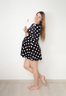 Beautiful smiling pregnant woman in cute dress posing with lollipop