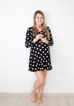 Beautiful smiling pregnant woman holding big lollipop