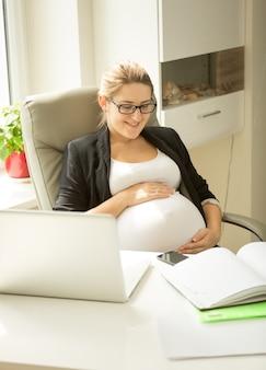 デスクのオフィスでポーズをとって美しい笑顔の妊婦