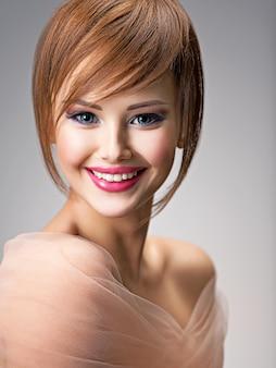 スタイルの髪型を持つ美しい笑顔の赤毛の女の子。大きな青い目をしたセクシーな若い女性の肖像画。ファッションモデルのポーズ