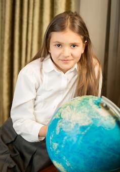 キャビネットで地球儀とポーズをとって美しい笑顔の女子高生