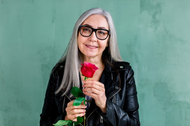 Beautiful smiling senior lady with long straight gray, wearing eyeglasses and stylish leather jacket, posing on camera, standing on green wall background, holding fresh red rose in hand