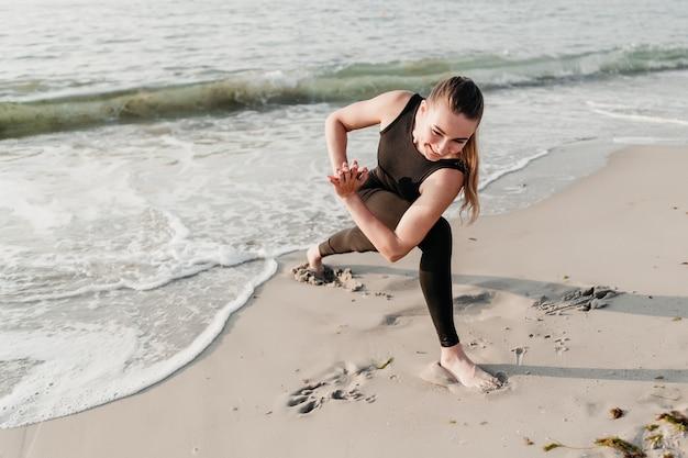海の近くのビーチでヨガをやっている笑顔のスポーティな美人