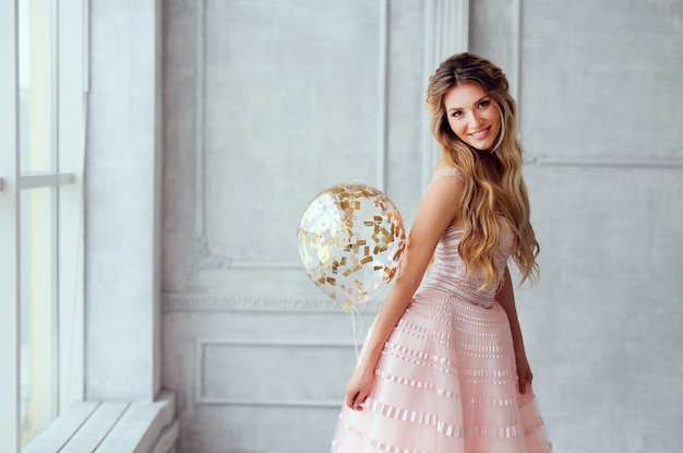 Beautiful smiling spring girl in a pink dress with balloons