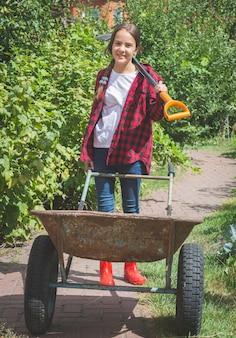 庭で働く長靴の美しい笑顔の十代の少女