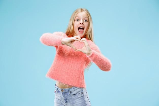 La bella ragazza teenager sorridente fa la forma di un cuore con le sue mani sull'azzurro.