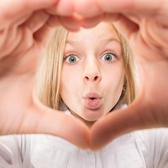 La bella ragazza teenager sorridente fa la forma di un cuore con le sue mani sui precedenti rosa. gesto d'amore da bambino piuttosto piccolo.