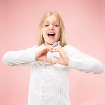 Beautiful smiling teen girl makes the shape of a heart with her hands on the pink background. gesture of love by pretty young child.