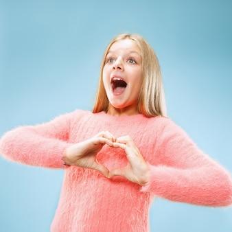 美しい笑顔の十代の少女は、青い背景に彼女の手でハートの形を作ります。かなり幼い子供による愛のしぐさ。