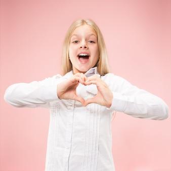 美しい笑顔の十代の少女は、ピンクの背景に彼女の手でハートの形を作ります。かなり幼い子供による愛のしぐさ。