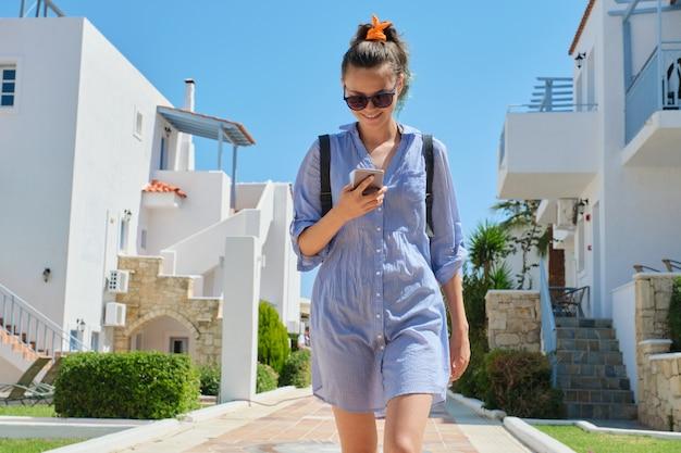 スマートフォンを使用して歩く美しい笑顔の十代の少女、晴れた夏の日