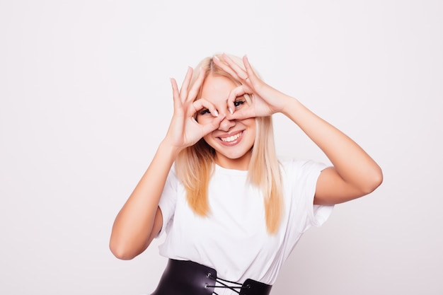 美しい笑顔の10代の少女は指からメガネを示しています。