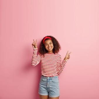 Bello adolescente sorridente con capelli ricci che posano in maglione rosso a strisce