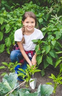 Красивая улыбающаяся девочка-подросток, работающая в саду с ручной лопатой