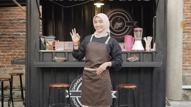 Красивая улыбающаяся официантка готова открыть контейнер для будки кафе