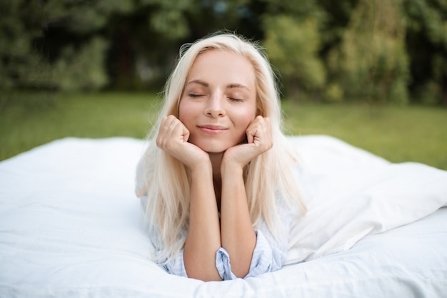 Beautiful smiling wear pajamas lying in bed outdoors