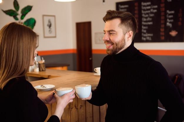 コーヒーショップで時間を過ごしながらコーヒーを飲む美しい笑顔の女性と男性。