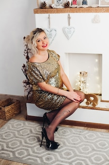 Beautiful smiling woman in bright golden dress sitting at fireplace.