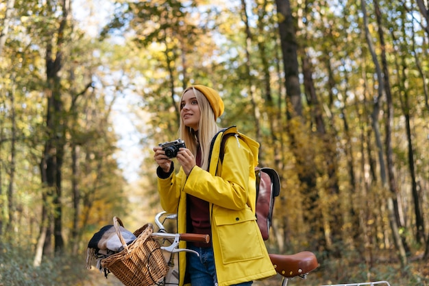 Beautiful smiling woman cycling in autumn forest photographer taking pictures in park