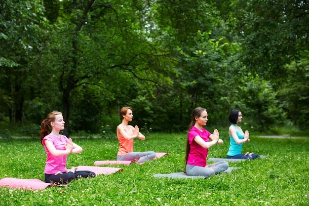 Beautiful smiling woman doing yoga in the park.