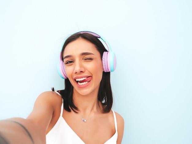 白いパジャマを着た美しい笑顔の女性。ワイヤレスヘッドホンで音楽を聴くのんきなモデル