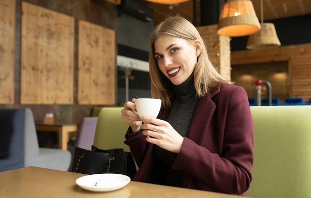 Красивая усмехаясь женщина пьет кофе в кафе.