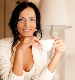 Beautiful smiling woman drinking coffee. home.