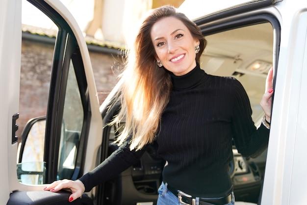 Beautiful smiling woman driving motor rv campervan home van in vanlife style concept