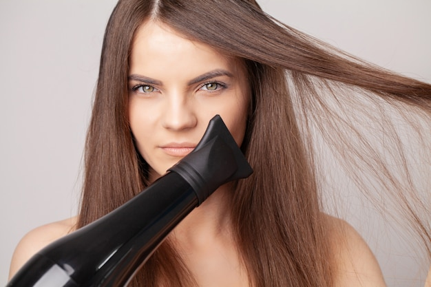Beautiful smiling woman drying her long hair with dryer