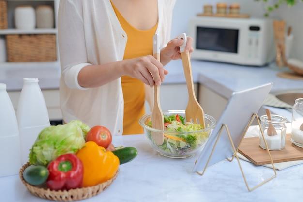 Красивая улыбающаяся женщина ест овощи, делая салат по рецепту на планшетном компьютере на кухне
