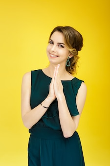 Beautiful smiling woman in green dress on yellow background. positive emotions