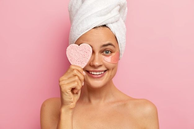 Beautiful smiling woman has well cared body, covers eye with sponge, applies collagen patches, wears white towel on head