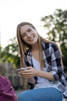 Beautiful smiling woman holding cellphone, chatting, communication, shopping online