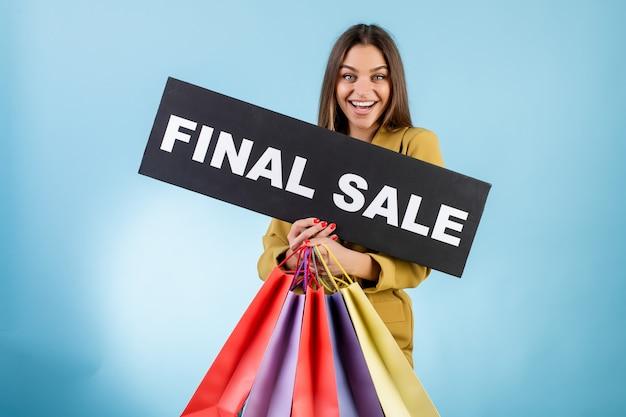 Красивая усмехаясь женщина держа знак окончательной продажи copyspace черный и красочные хозяйственные сумки изолированные над синью