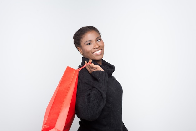Beautiful smiling woman holding shopping bag on shoulder