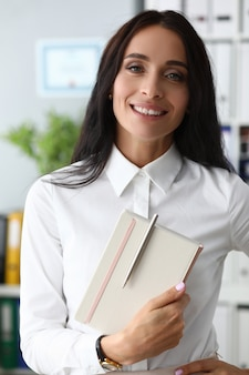 Beautiful smiling woman holds trendy notebook