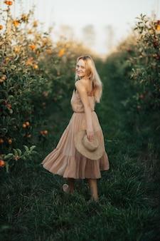 優しいドレスを着た美しい笑顔の女性がリンゴ園を散歩します。リンゴ園で麦わら帽子と笑顔の夏の女性。