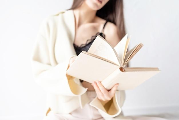 笑顔で床に座って本を読んで快適な家庭服を着た美しい笑顔の女性