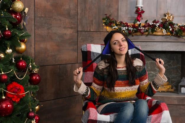 装飾された暖炉のあるリビングルームのクリスマスツリーの近くのロッキングチェアに座っている面白いニット北欧の帽子の美しい笑顔の女性