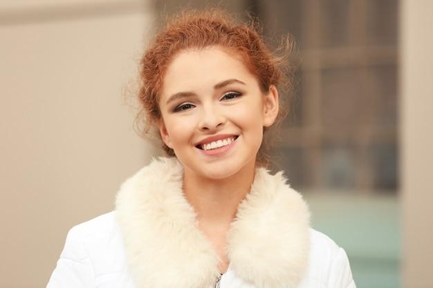 야외에서 가짜 모피 칼라와 재킷에 아름 다운 웃는 여자
