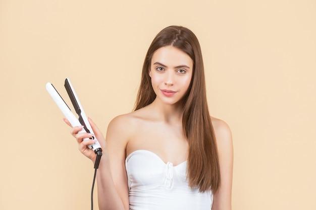 Красивая улыбающаяся женщина, гладящая длинные волосы с утюгом. женщина, выпрямляющая волосы с помощью выпрямителя. портрет молодой красивой девушки, использующей стайлер на ее сияющих волосах. прическа