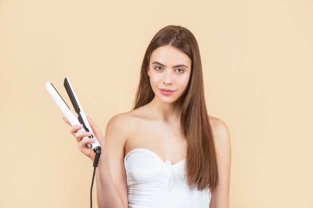 Beautiful smiling woman ironing long hair with flat iron. woman straightening hair with straightener. portrait of young beautiful girl using styler on her shining hair. hairstyle
