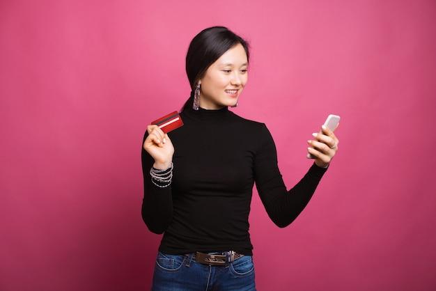 美しい笑顔の女性は、彼女のカードで支払いをオンラインショッピング彼女の電話を見ています。