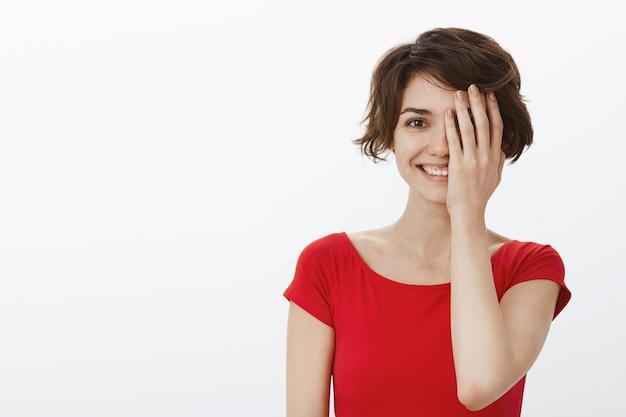 Bella donna sorridente che sembra felice, coprire metà del viso con il palmo
