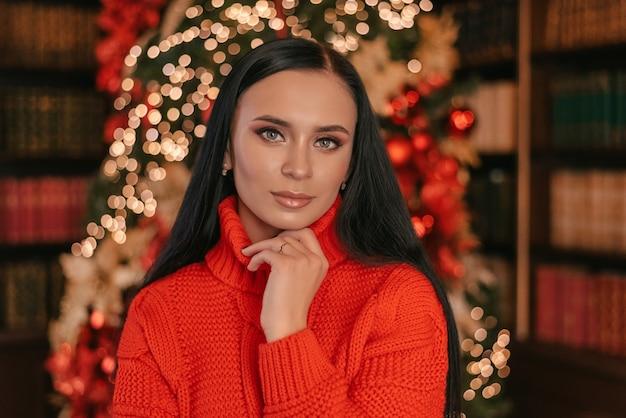 美しい笑顔の女性モデルは健康的な長い髪型を構成しますクリスマスツリーのライトを背景に赤いセーターを着たエレガントな女性明けましておめでとうございます