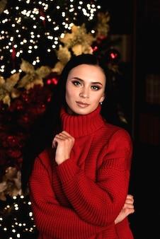 美しい笑顔の女性モデルメイク健康的な長い髪のスタイルクリスマスツリーの上の赤いドレスのエレガントな女性