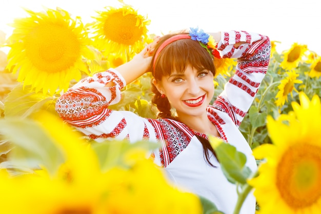 Beautiful smiling woman in national ukrainian blouse embrodery looking to camera on a sunflower field at sunset