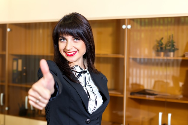 Beautiful smiling woman in office shows thumb up