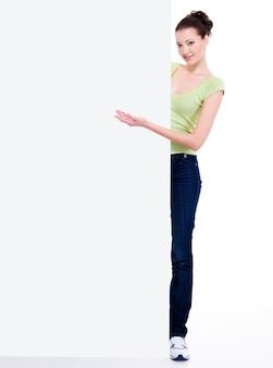 La bella donna sorridente indica a mano il tabellone per le affissioni in bianco